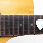Guitar plectrum on guitar — Stock Photo
