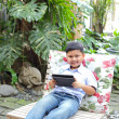 Foto de Stock  : Asiboy playing tablet at park