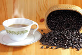 Coffee cup and coffee bean on a wooden table — Stock Photo