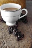 Xícara de café e feijão de café em uma mesa de madeira — Fotografia Stock