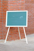 Chalk board front red brick wall — Stock Photo