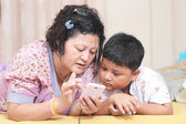 Asian mother and son. Playing smart phones — Stock Photo