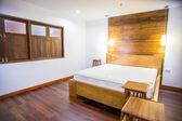 Bedroom interior with white bedding and hardwood floor — Stock Photo