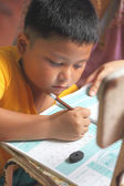 The boy work homework carefully — Stock Photo