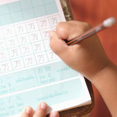 Hand of little boy work homework carefully — Stock Photo