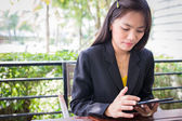 Beautiful Asian business woman using tablet for communication — Foto de Stock