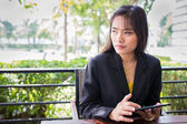 Beautiful Asian business woman using tablet for communication — Stock Photo