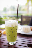 Green tea smoothie on wooden table, natural backdrop — Stock fotografie