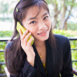 Asiyoung businesswomen Are using phone to communicate — Stock Photo #40592327