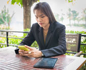 Beautiful Asian business woman using mobile for communication — Photo