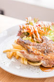 Pork steak and French fries topped with sauce — Foto Stock