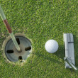 Putter puts a golf ball to hole on green of golf course — Stock Photo