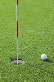 Putter coloca uma bola de golfe com buraco no green do campo de golfe — Foto Stock