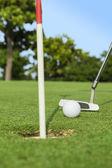паттер кладет мяч для гольфа отверстия на зеленом поле для гольфа — Стоковое фото