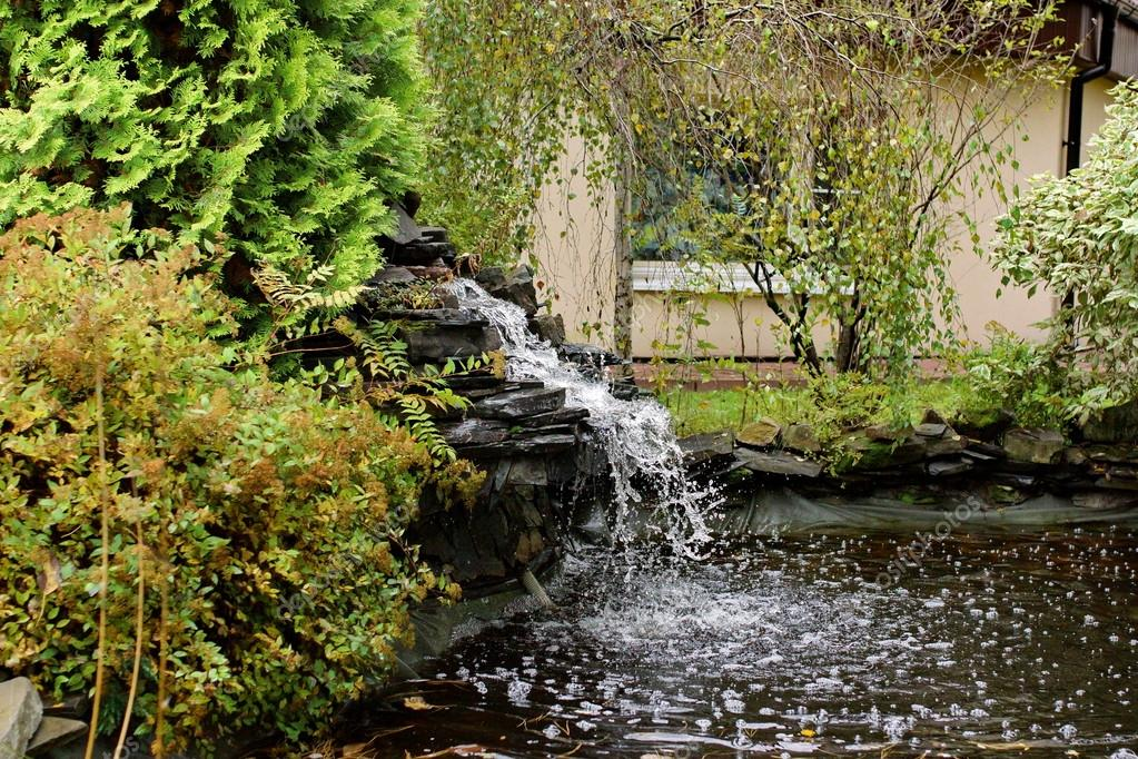 Artificial pond and waterfall in backyard garden stock for Artificial plants for outdoor ponds