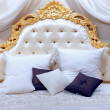 Luxurious king-size bed with gold-patterned headboard — Stock Photo