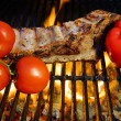 Stock Photo: Ribs roasted in barbecue with pepper and tomatoes