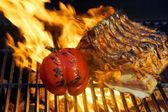 Ribs with vegetables in the flame on the grill — Stock Photo