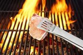 Bone steak, Tongs and Hot BBQ Grate with Flames — Stockfoto