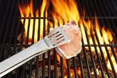 Bone steak, Tongs and Hot BBQ Grate with Flames — Stock fotografie