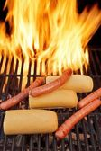 Hot dogs on the BBQ grill under flaming coals, XXXL — Stock Photo