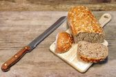 Cereal Bread Loaf with Grains and slicer knife in rustic still-l — Stock Photo