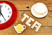 Tea cup, clock and sign made from sugar on brown wooden table — Stock Photo