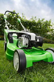 Green lawnmower on green lawn. — Stock Photo