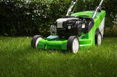 Green lawnmower on green lawn — Stock Photo