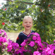 Child among the flowers in the garden — Stock Photo