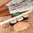 Sushi and a fan with Japanese characters — Stock Photo #29373963