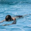 Teenager swims in the pool — Stock Photo #49496693
