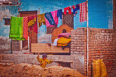 Poor indian house with colorful clothes — Stock Photo