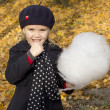 Beautiful girl eating cotton candy at the autumn park — Stok fotoğraf