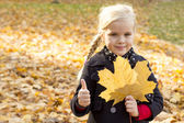 Girl with autumn leaf in hand — Stock Photo