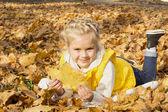 Beautiful cheerful girl among autumn leaves — Stock Photo