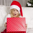 Girl opening Christmas gift — Stock Photo