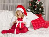 Girl hat opening Christmas gift — Stock Photo