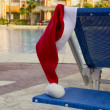 Santa claus hat hanging on a sunbed near the pool — Stock Photo
