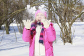 Beautiful girl fooling around with snow in park — Stock Photo