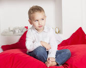 Angry boy sitting on a bed — Stock Photo