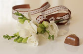 Sprig of freesia flower and chocolates — Stock Photo