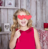 Beautiful girl in red dress smiling with hearts — Stock Photo