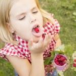 Girl holding raspberries in her hand — Stock Photo #49517105