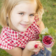 Girl holding raspberries in her hand — Stock Photo #49517111