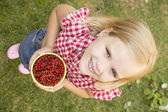 Girl holding a red currant — Stock Photo