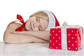 Girl dressed as Santa sleeps — Stock Photo