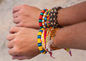 Colorful bracelets on their hands — Stock Photo