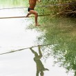 图库照片: People walk on tightrope Slackline