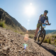 Stock Photo: People in mountains on bike races to victory